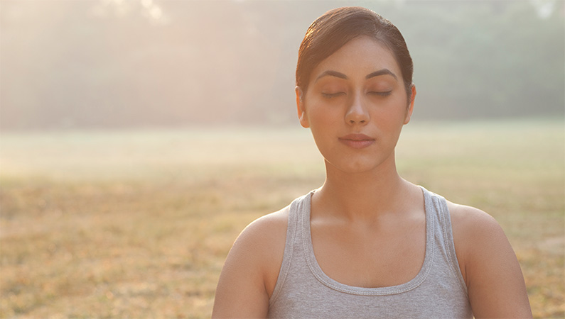 Woman meditating outside,