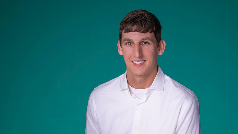 Male wearing white button-up shirt smiling in front of green background