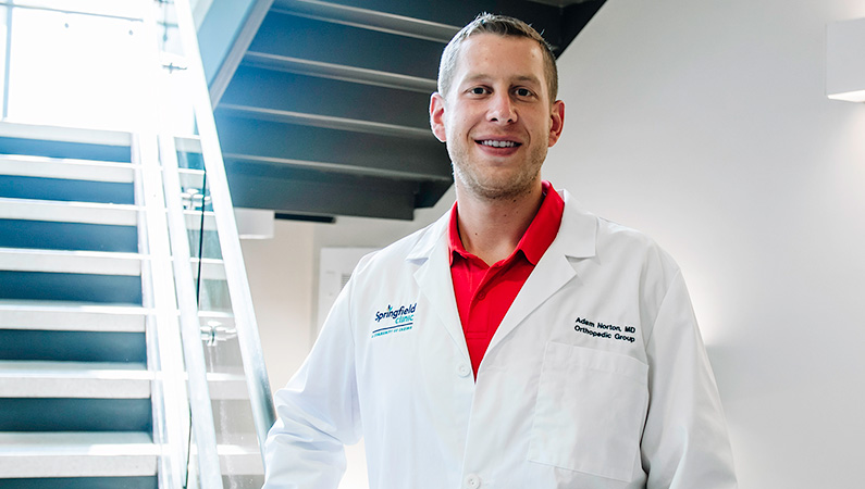 Man wearing a white doctors coat smiling in front of stairs.