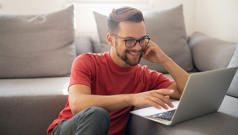 Male wearing glasses smiling while working on a laptop on a couch