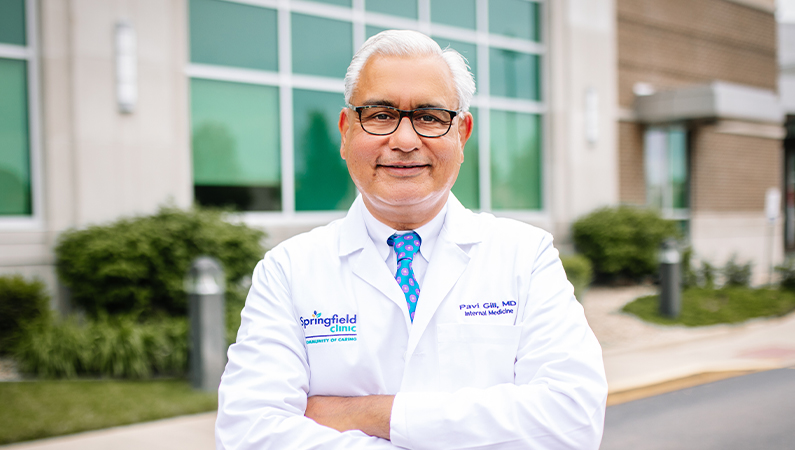 Male wearing glasses and white medical coat smiling in outdoor setting in front of medical building