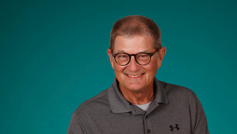 Male wearing glasses smiling in front of green background