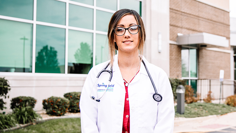 Woman standing outside, smiling in front of the doctors office.