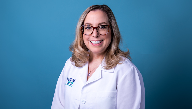 Female with light hair wearing glasses and white medical coat smiling in front of blue background