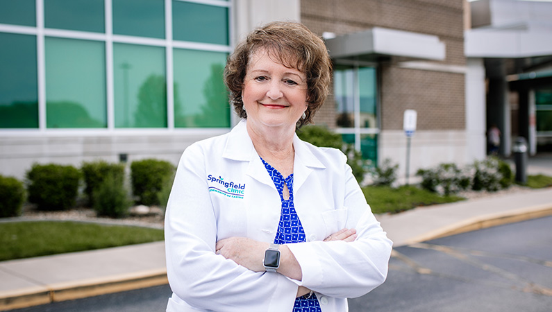 Female with short dark hair wearing white medical coat posing in outdoor setting