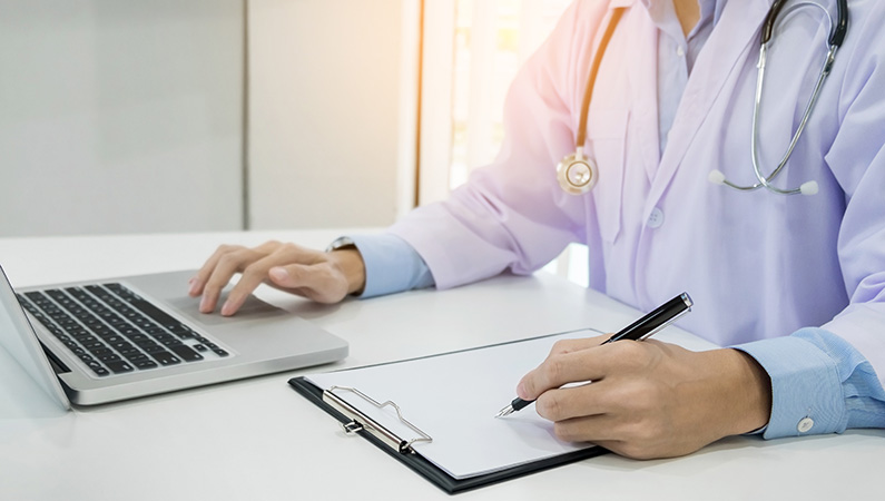 Individual wearing medical coat and stethoscope on computer and writing information down on clipboard