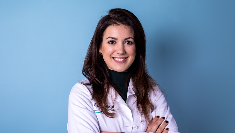 Female with dark hair wearing white medical coat smiling in front of blue background