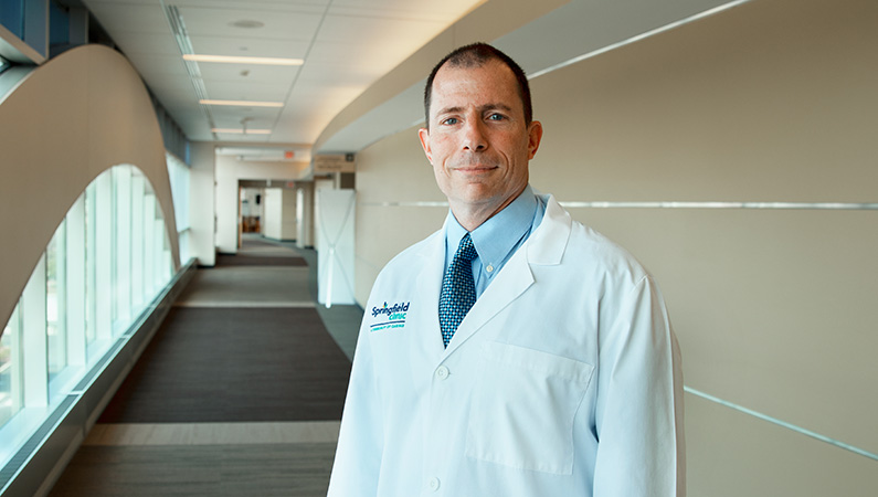 Male wearing white medical coat posing in well-lit hallway