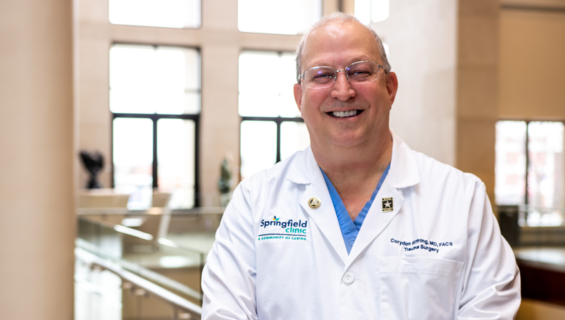 Male wearing glasses and white medical coat smiling in a medical office building setting