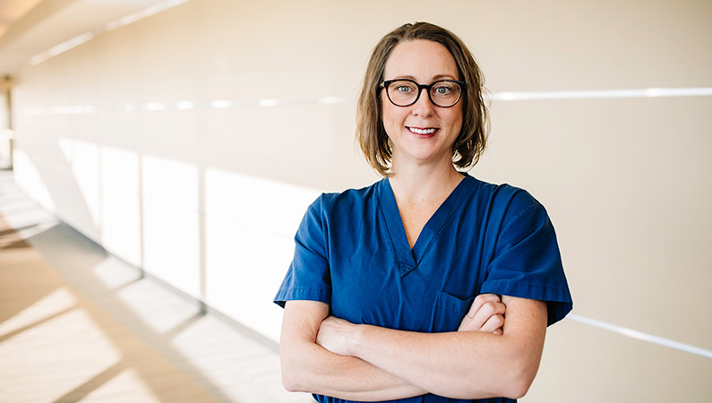 Female medical professional with short brown hair and glasses and arms crossed smiling in a hallway