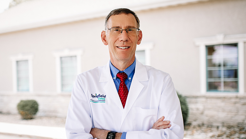 Male physician in white coat smiling in bright outdoor setting