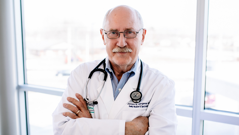 Male wearing glasses and stethoscope with white medical coat with arms folded posing in front of windows