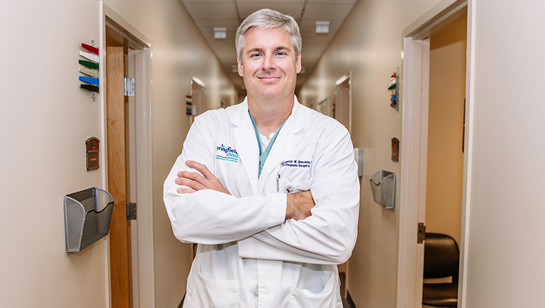 Male wearing white medical coat posing in medical office hallway