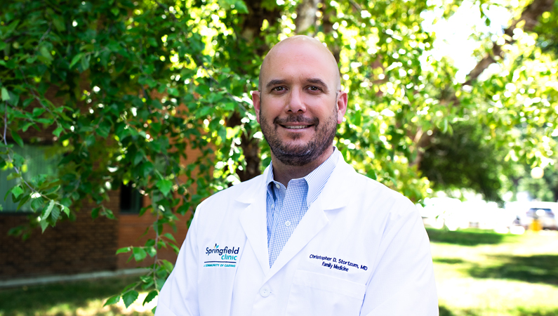 Male wearing white medical coat smiling in outdoor setting