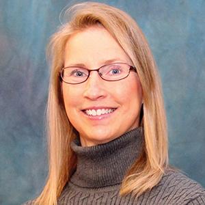 Blonde female smiling with glasses professional headshot
