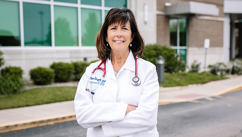 Female with short dark hair wearing white medical coat and stethoscope smiling in outdoor setting
