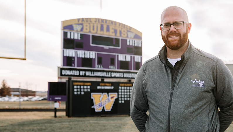 Male wearing glasses and sports zip up smiling in on football field in front of scoreboard