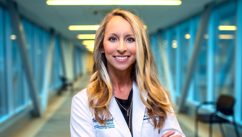 Female with wavy hair wearing a white medical coat smiling in a walkway