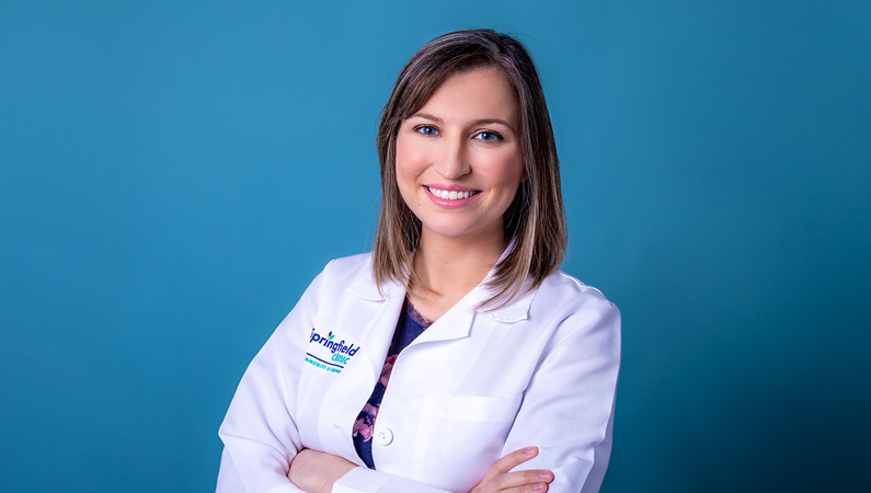 Female with short dark hair wearing white medical coat smiling in front of blue background