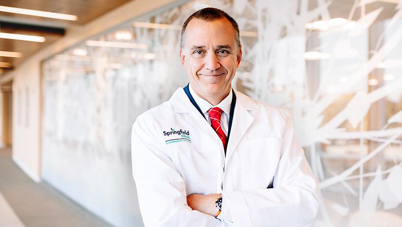 Male wearing white medical coat posing in well-lit walkway.